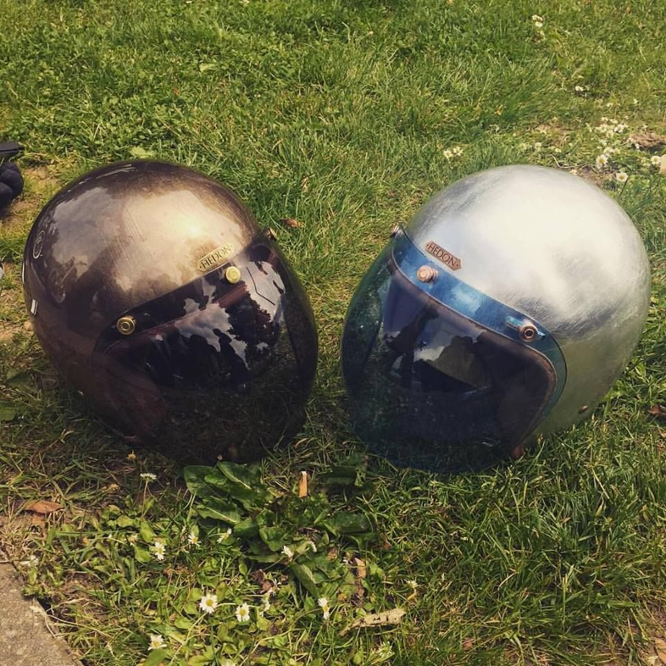 Hedonist Gladiator and Silver Lining taking a break in the sun enroute to Biarritz. Looking so fine with their Desert Smoke and Amber bubbles. 😍 #hedon #hedonhelmets #metallicleaf #crashhelmets #gladiator #silverlining #brasshardware #copperhardware #customhelmet #custombikes #epicroadtrip @wheels_and_waves
