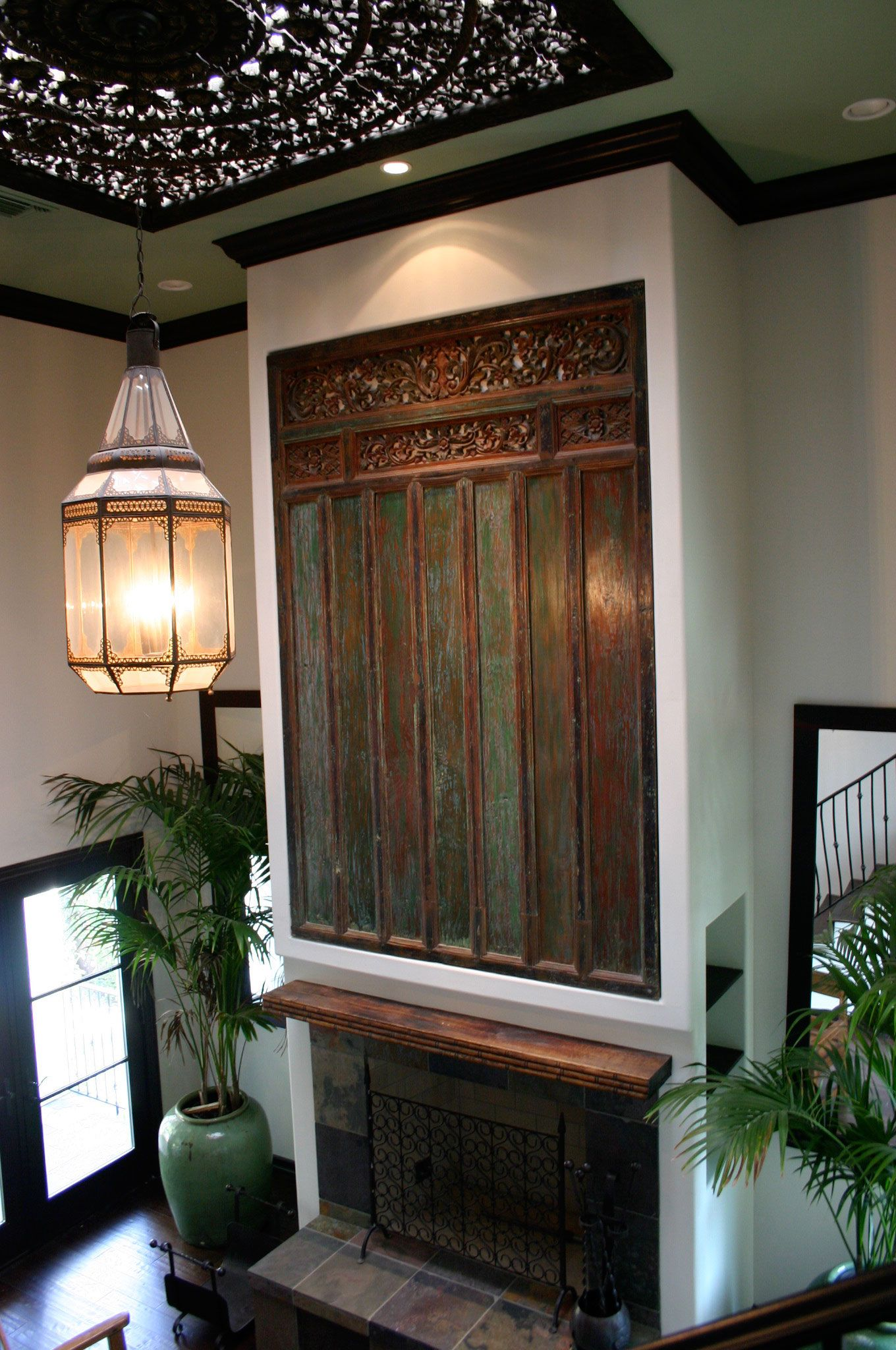 Antique carved indonesian door panel above fireplace bali and