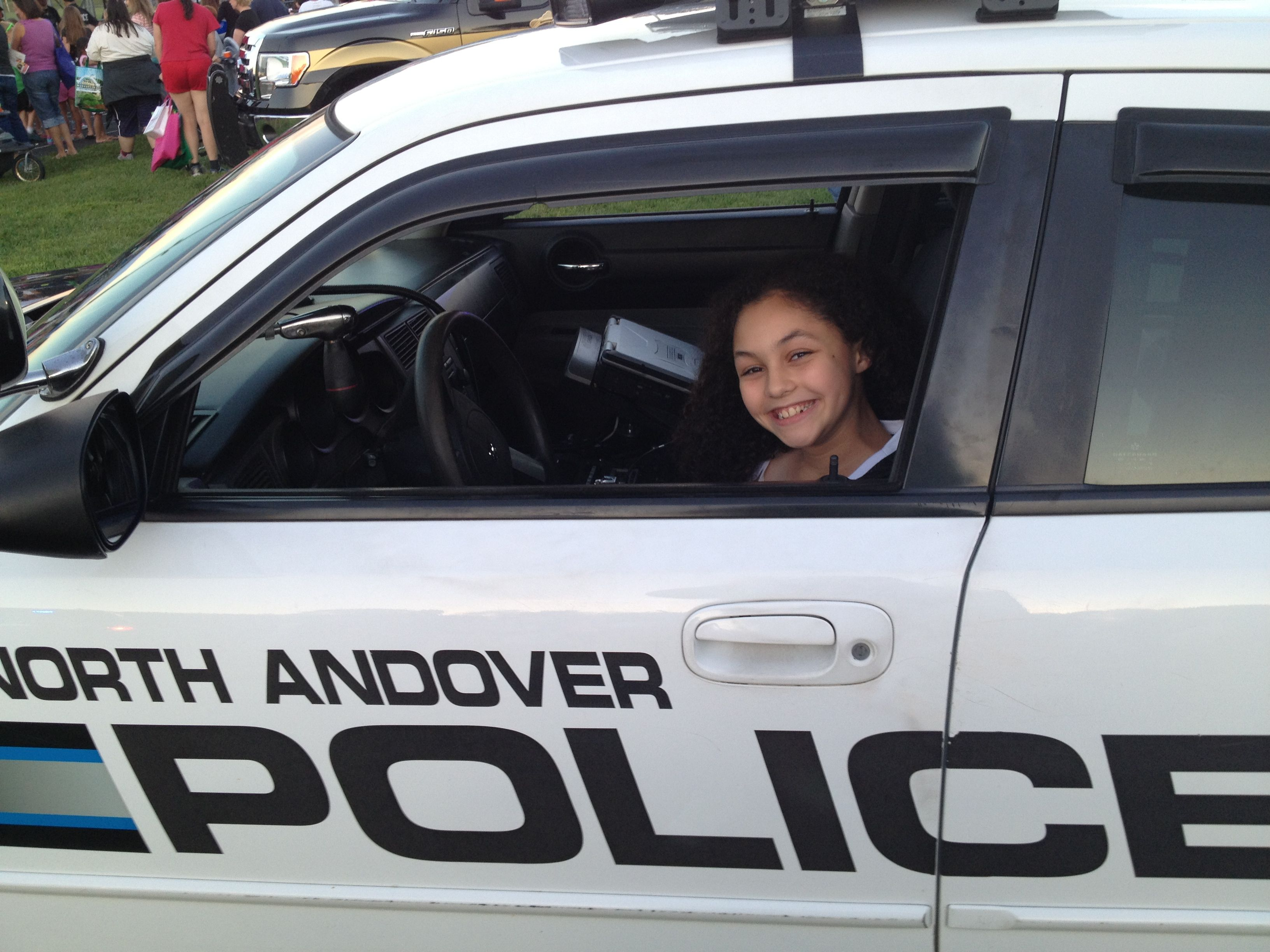 """Carly """"driving"""" the police cruiser."""