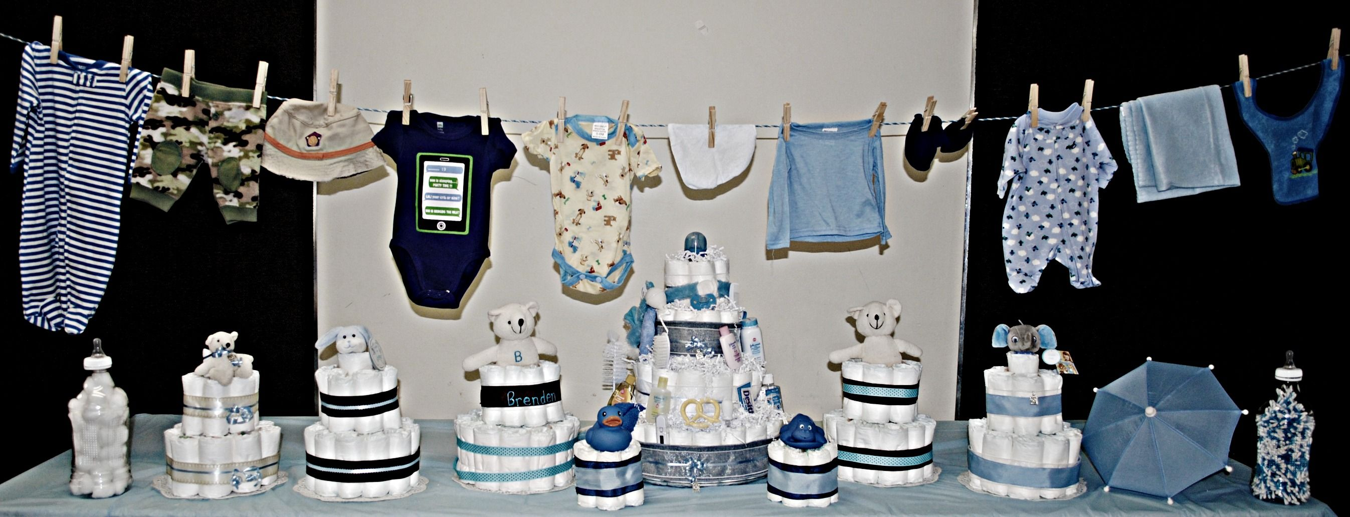 Baby Boy Shower set-up.  Smaller cakes are used as centerpieces for guest tables, over-sized bottles (made from v-8 splash bottles) were filled with cotton balls or q-tips and set out for guests to estimate the amount inside(as a game).  All are pictured below baby boy clothes that are hung from clothesline(baby blue rope from Dollar Tree).