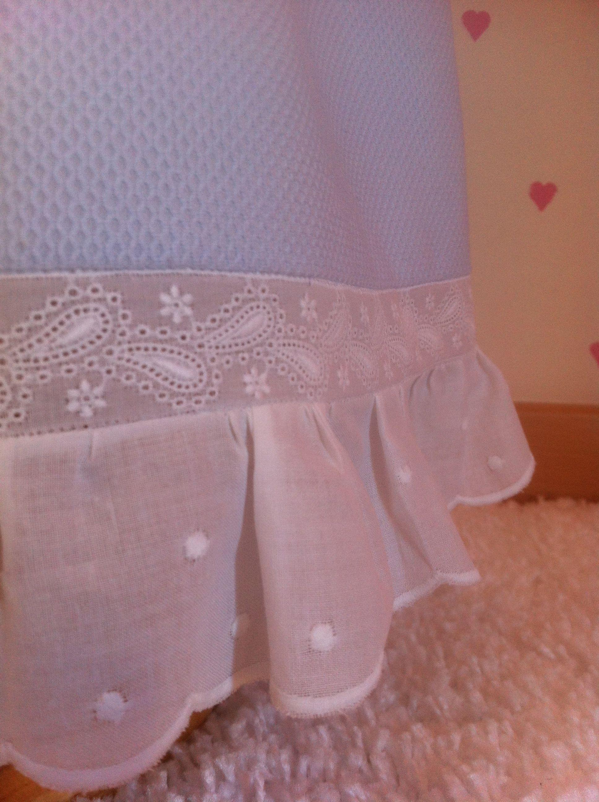 Detalle del piqué azul bebé rematado por entredós y tira bordada en algodón blanco