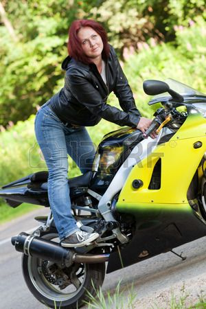 beautiful young woman standing at the roadside near the sports motorcycle