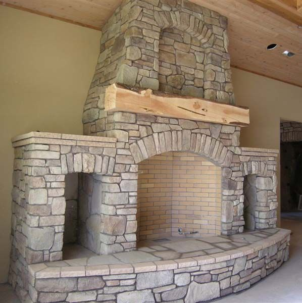 fireplace with built in wood storage niches and rough hewn mantle