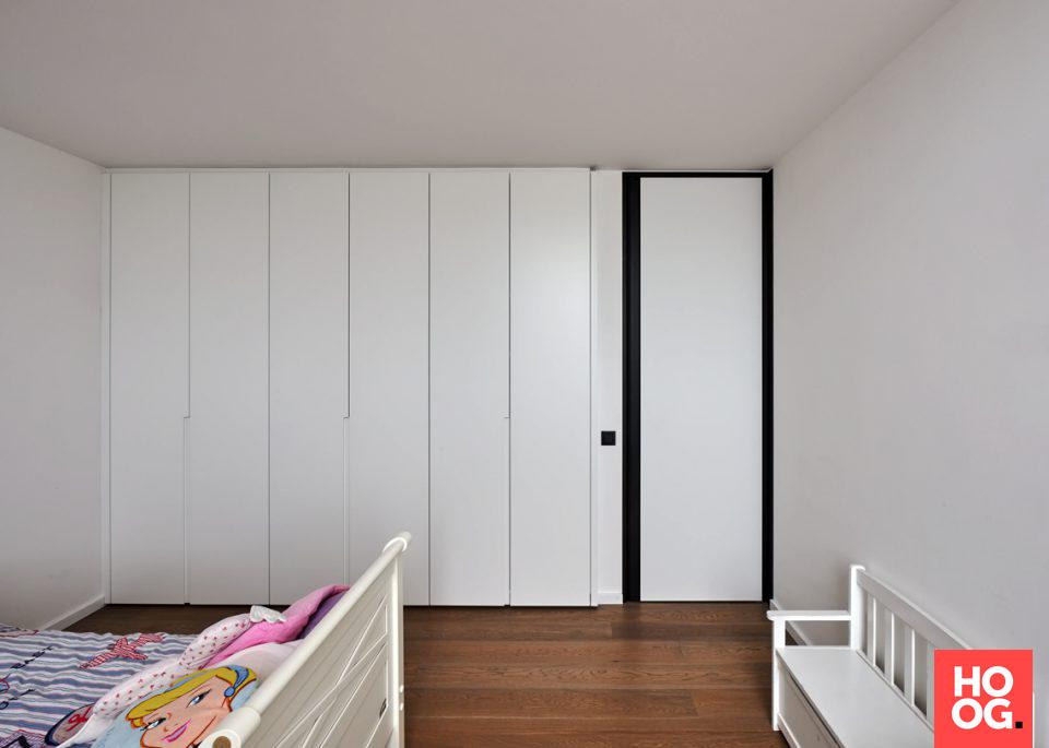 Slaapkamer met witte deur en houten vloer deuren