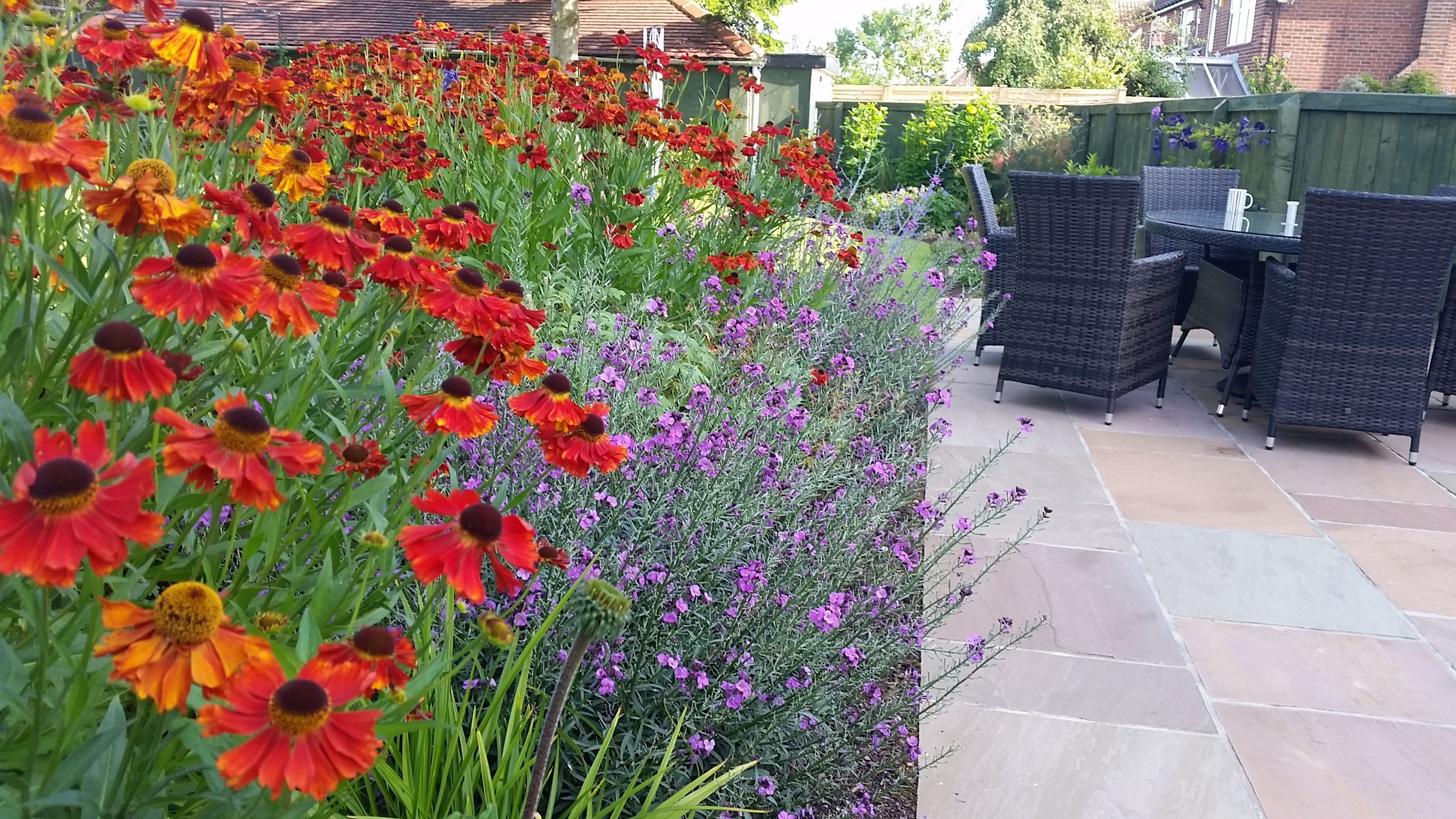 indian sandstone patio with colourful flower border north leeds
