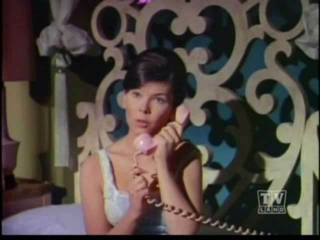 Barbara Gordon on the phone. Ever notice the bat symbol in her headboard?