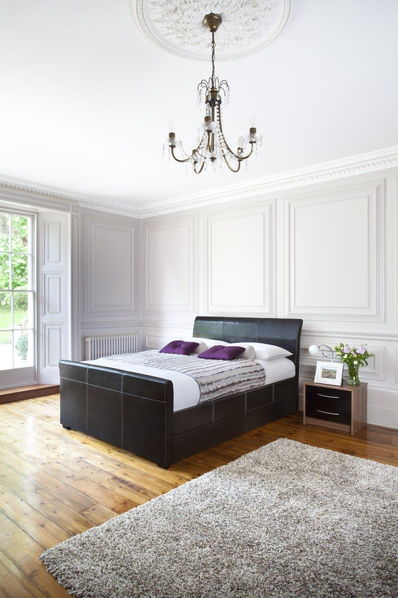 An Elegant Bedroom With A Faux Leather Bed, Sumptuous Plum Cushions And  Stylish Silver Rug