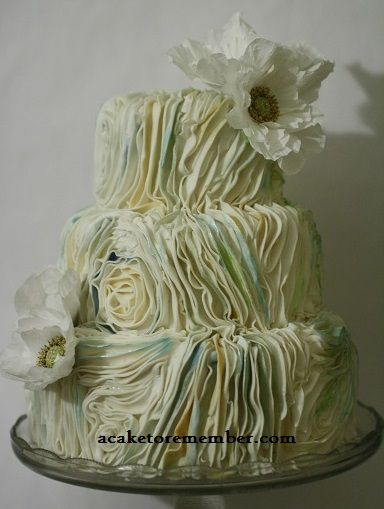 Cake with fondant ruching details and paper flowers by A Cake To