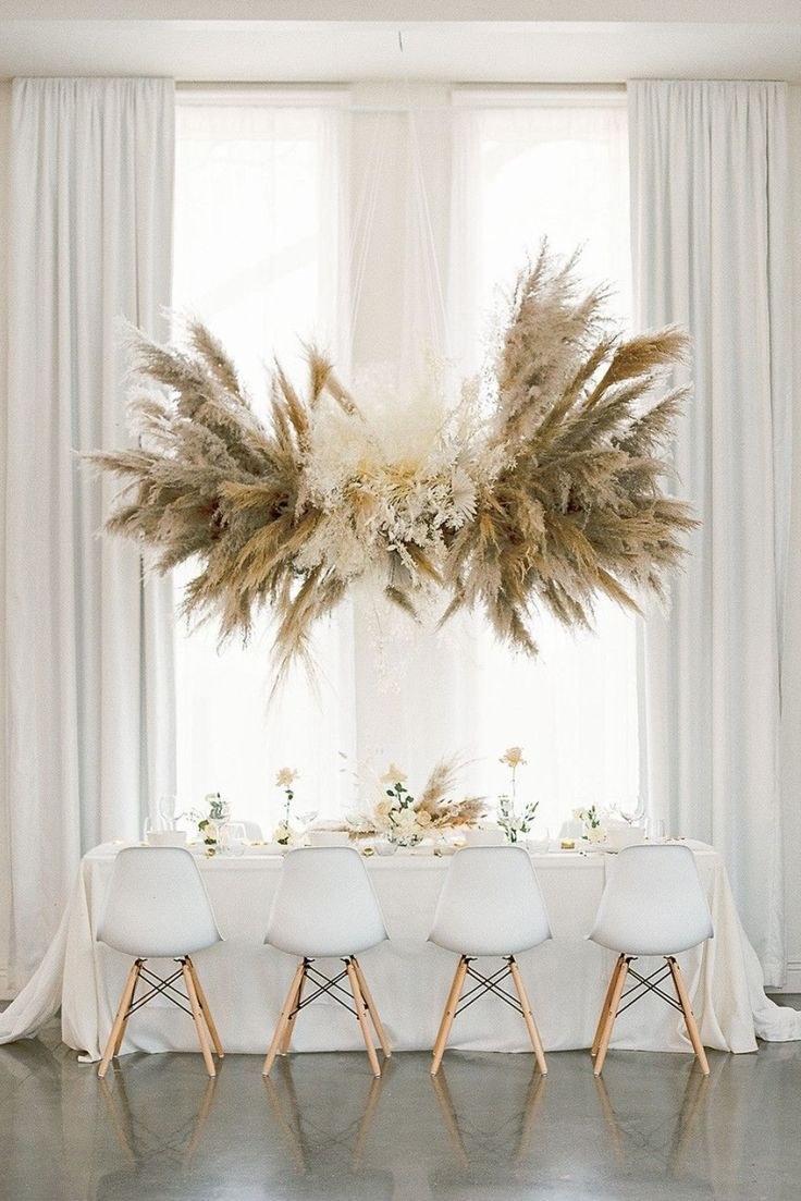 TABLE DECOR | NgLp Designs shares a modern, monochromatic wedding table — white-on-white theme, with large pampas grass installation, white linens and white iconic Eames Chairs. | Erin Wilson Photography |  table, table decor, tablesetting, wedding table /// #weddingtable #floraldecor #tabledecor