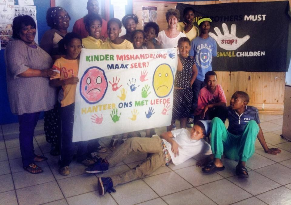 Volunteer Clare Taylor with the staff and children at the youth development center volunteer placement in Knysna with the posters the children made