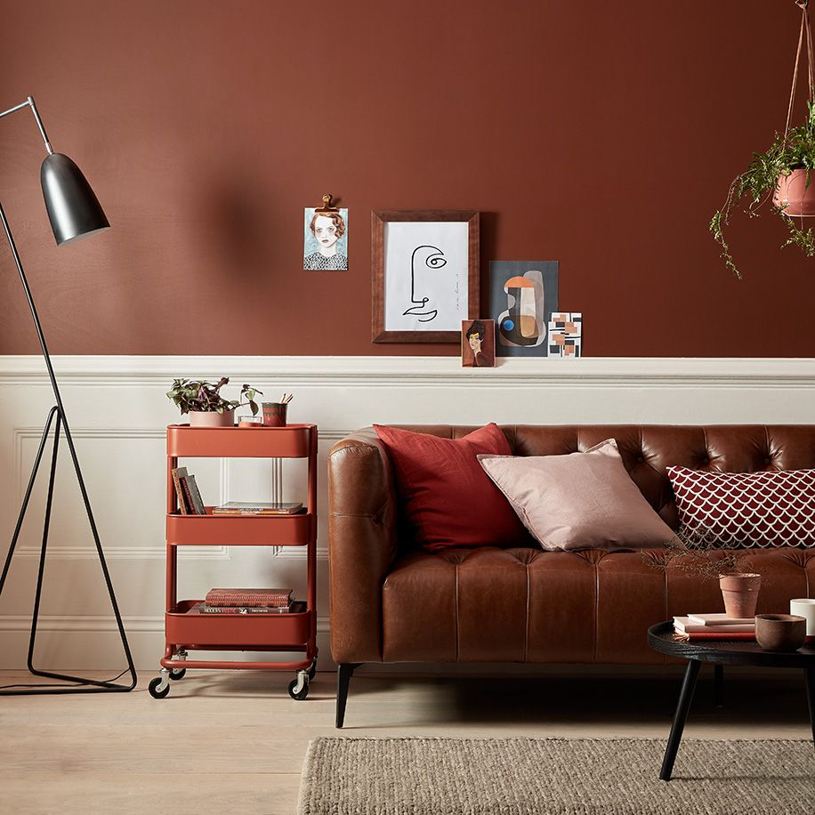 Dark Earthy Toned Walls Paired With A Leather Brown Sofa And Red Brown And Orange Accessories Living Room Warm Living Room Decor Brown Living Room #red #and #beige #living #room