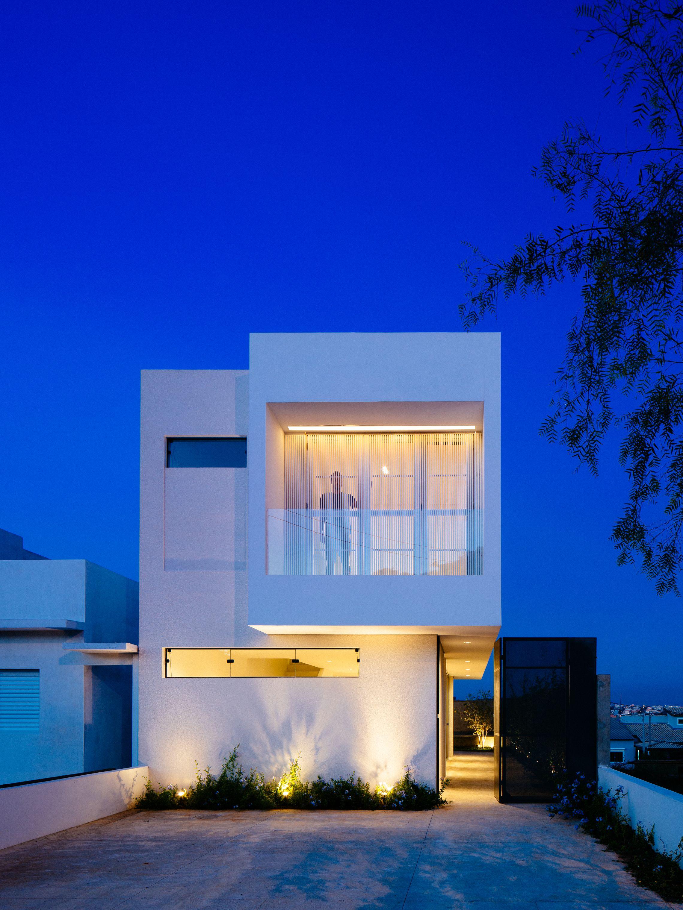 Sencilla casa de dos pisos construida en terreno peque o for Fachada de casas