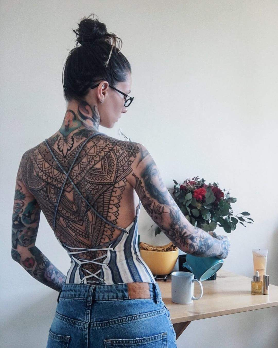 Photo of Back and arm tattoos.