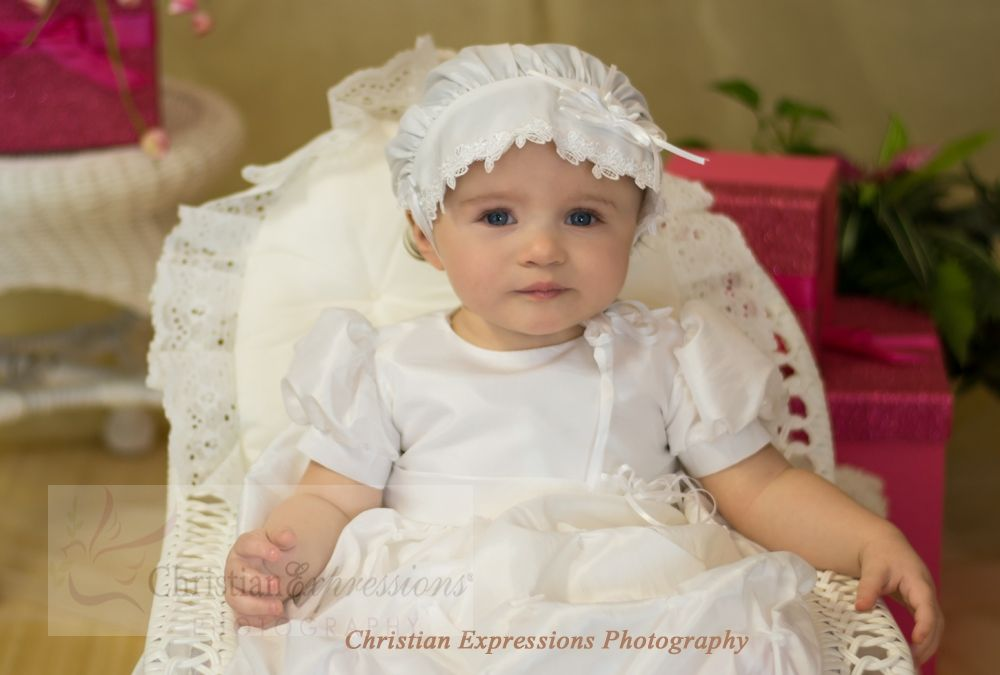 Charming  white christening gown with gathered rosette skirt and organza layered bodice. Includes matching bonnet. Fabricated of 100% polyester taffeta. . Made in the USA. Christian Expressions stocks this item (while supplies last) in sizes shown on our website.  http://www.christian-baby.com/pd-christening-gowns-destiny.cfm