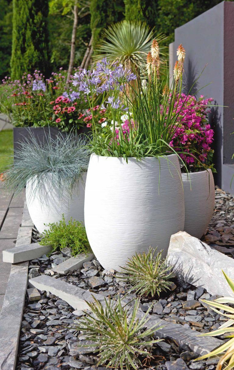 Photo of Contemporary fiber cement planters in brilliant white with colorful flowers and …