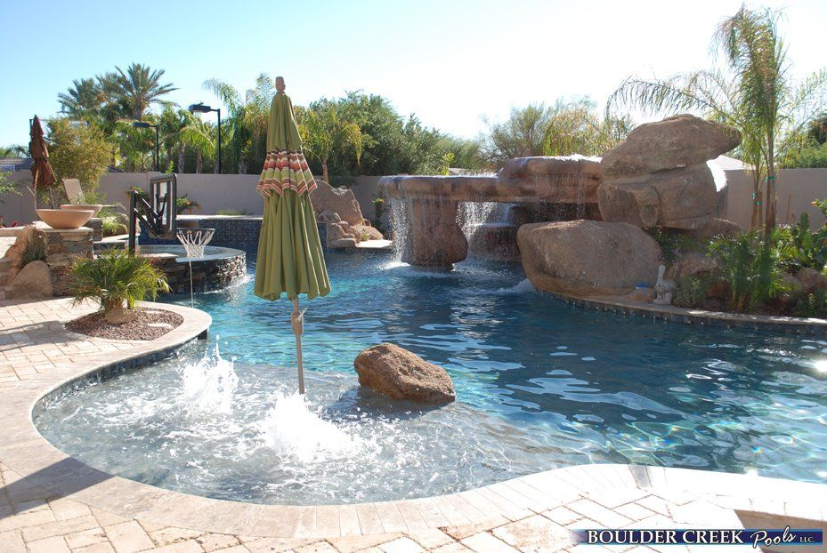 Love this extended shelf seating area with umbrella and mini fountains the rock feature is - Swimming pool designs with slides ...