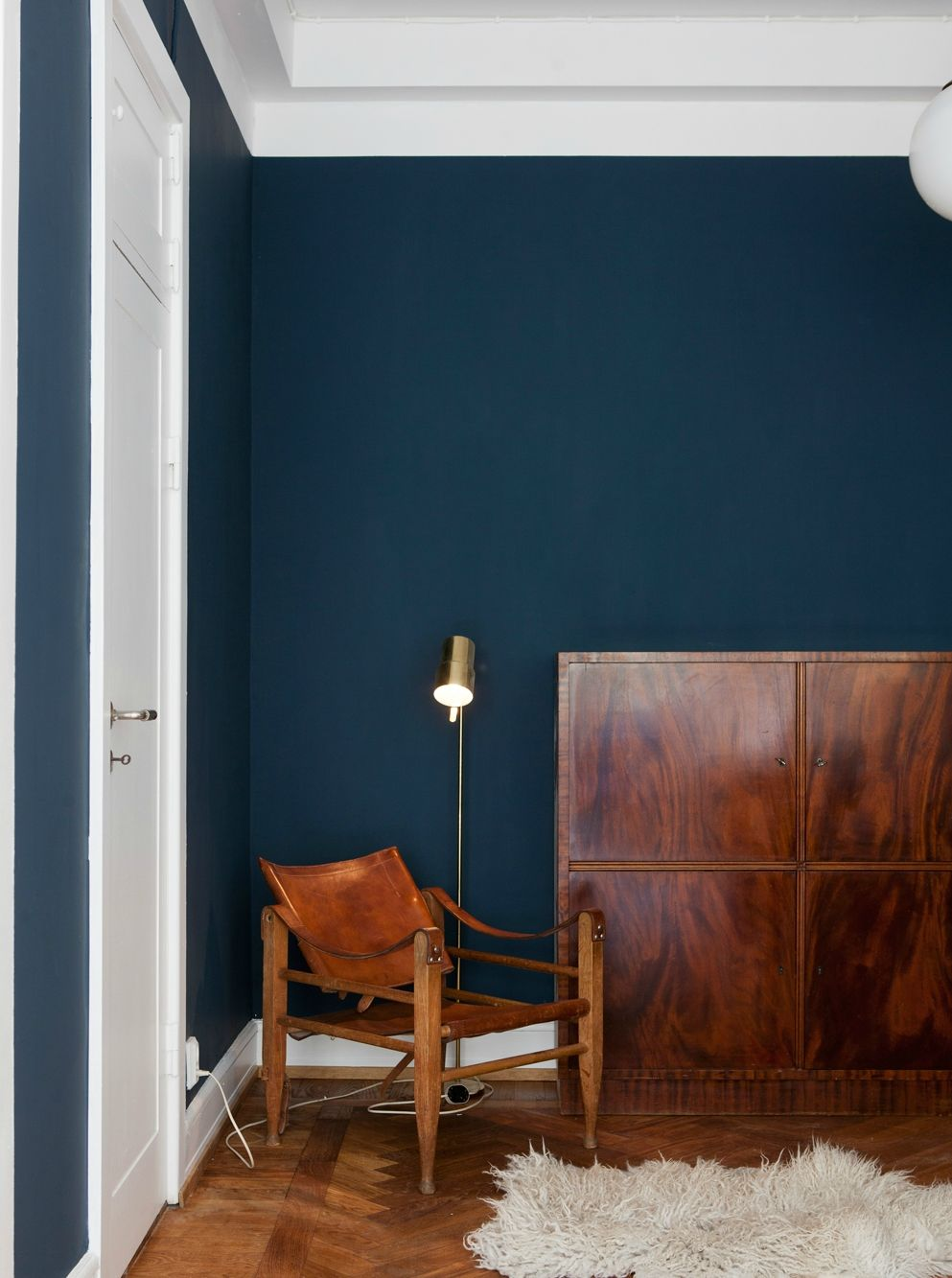 Cozy corner with leather chair and a dark blue wall for Dark walls white furniture