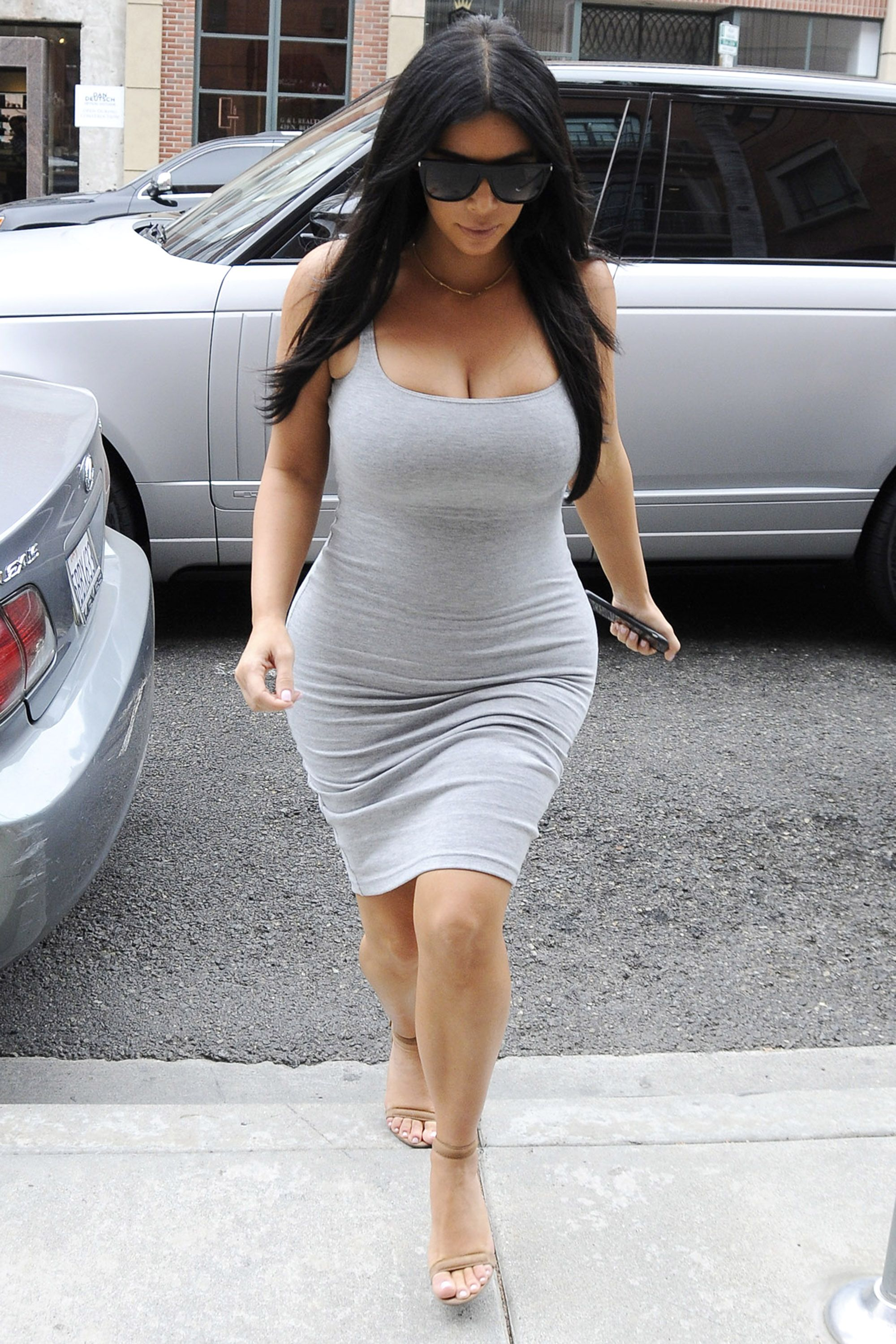 Kim kardashian is keeping up with sheer maternity looks tank in a gray tank dress and nude heels harpersbazaar ombrellifo Images