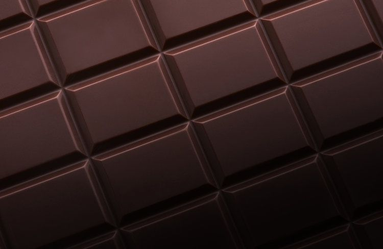 Still life photography of chocolate shot close up. Chocolate bar squares detail shot by London food photographer Josh Caudwell.