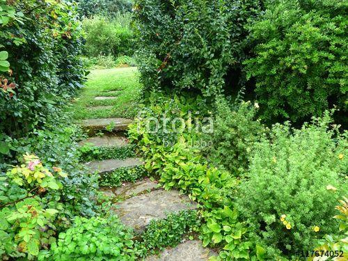 Durchgang mit Steinplatten in einem grünen Garten in ...