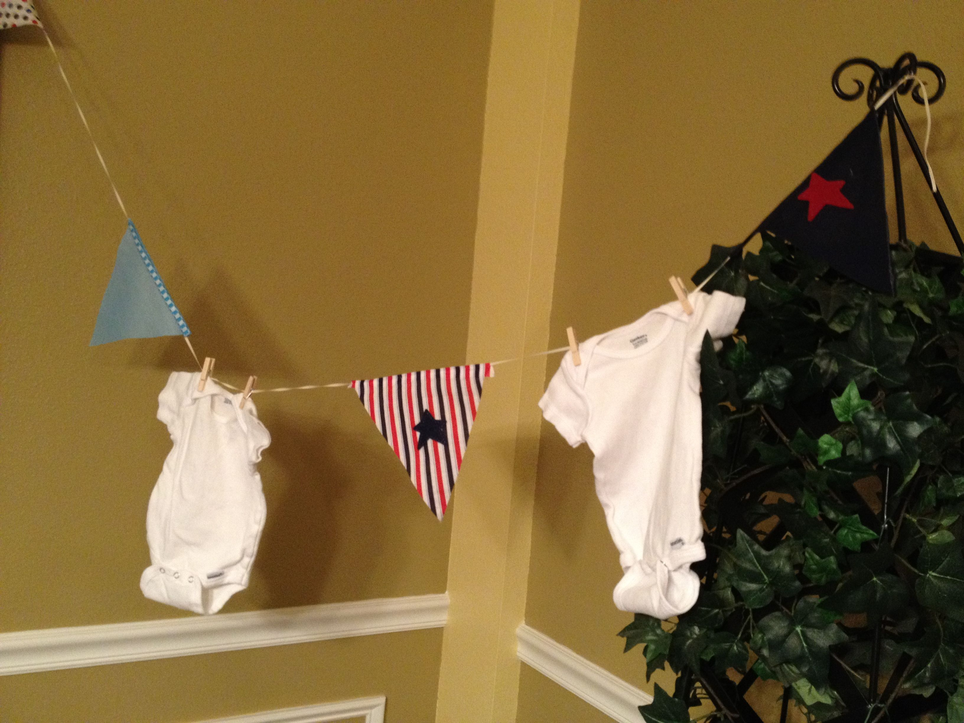 Close up of hanging onesies with nautical pennants for