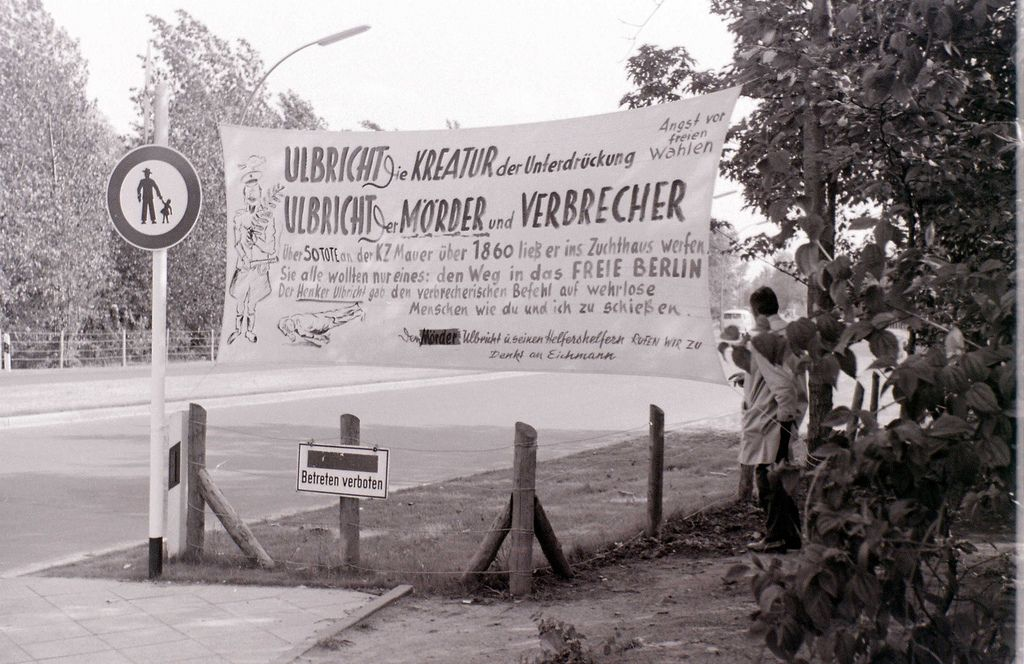 """Anti-Walter Ulbricht (East German leader) propaganda, probably in the Tiergarten near the sector border. The somewhat odd semi-permanent barbed wire fence across the footpath, which ends at that point at a """"Betreten verboten"""" notice, suggests that the footpath on the other side of the fence is technically on East Berlin territory, even though the roadway may not be. The Berlin Wall, although not visible here, would in that event be only a short distance away."""