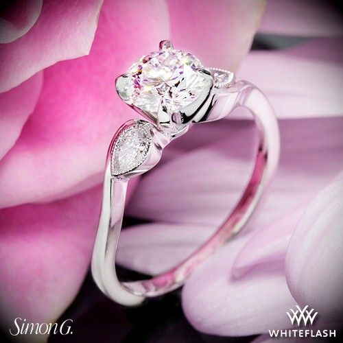 The Simon G MR2342 diamond engagement ring from the Duchess collection features two graceful pear shape diamonds tasteflully set in lightly millgrained bezels on either side of the center.