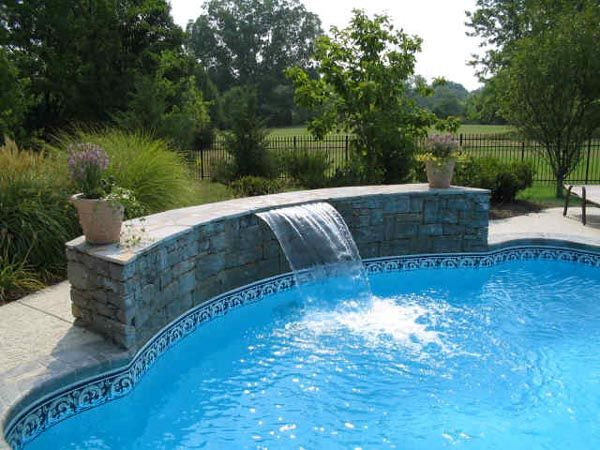 Swimming Pool Waterfall Designs pool awesome waterfall in swimming pool with natural stone wall design for outdoor decorating ideas Swimming Pool Designs Indoor Pool Serene Western Pool Nice Landscaping Nicely Lit Pool
