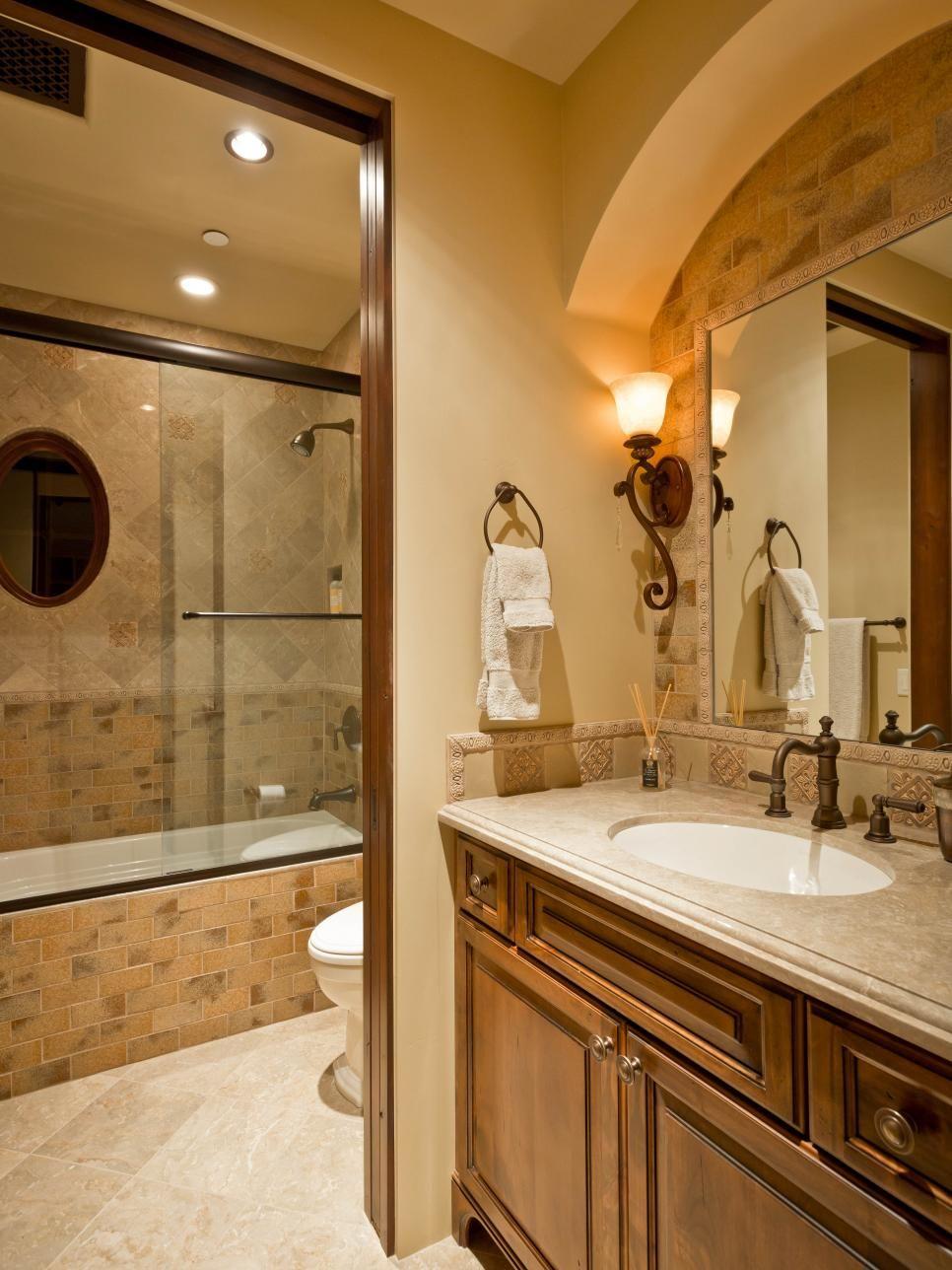 A Mediterranean bathroom is decorated in a warm, neutral palette ...
