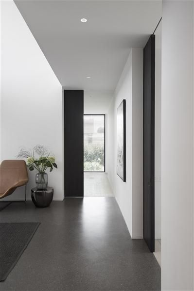 Grey toned interior with black sliding doors by Daskal Laperre