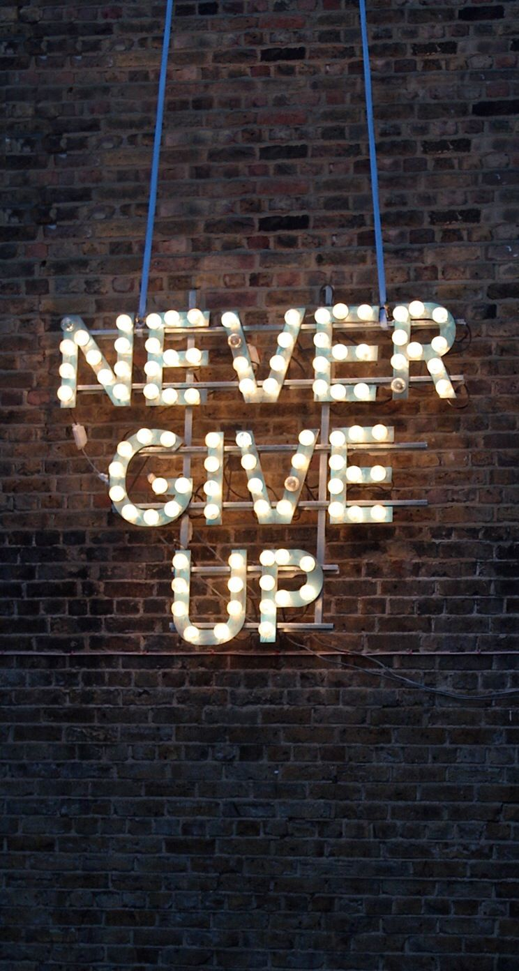 Brick Wall Marquee Lights Never Give Up Iphone Phone Background Wallpaper Lock Screen Words Words Quotes Cool Words