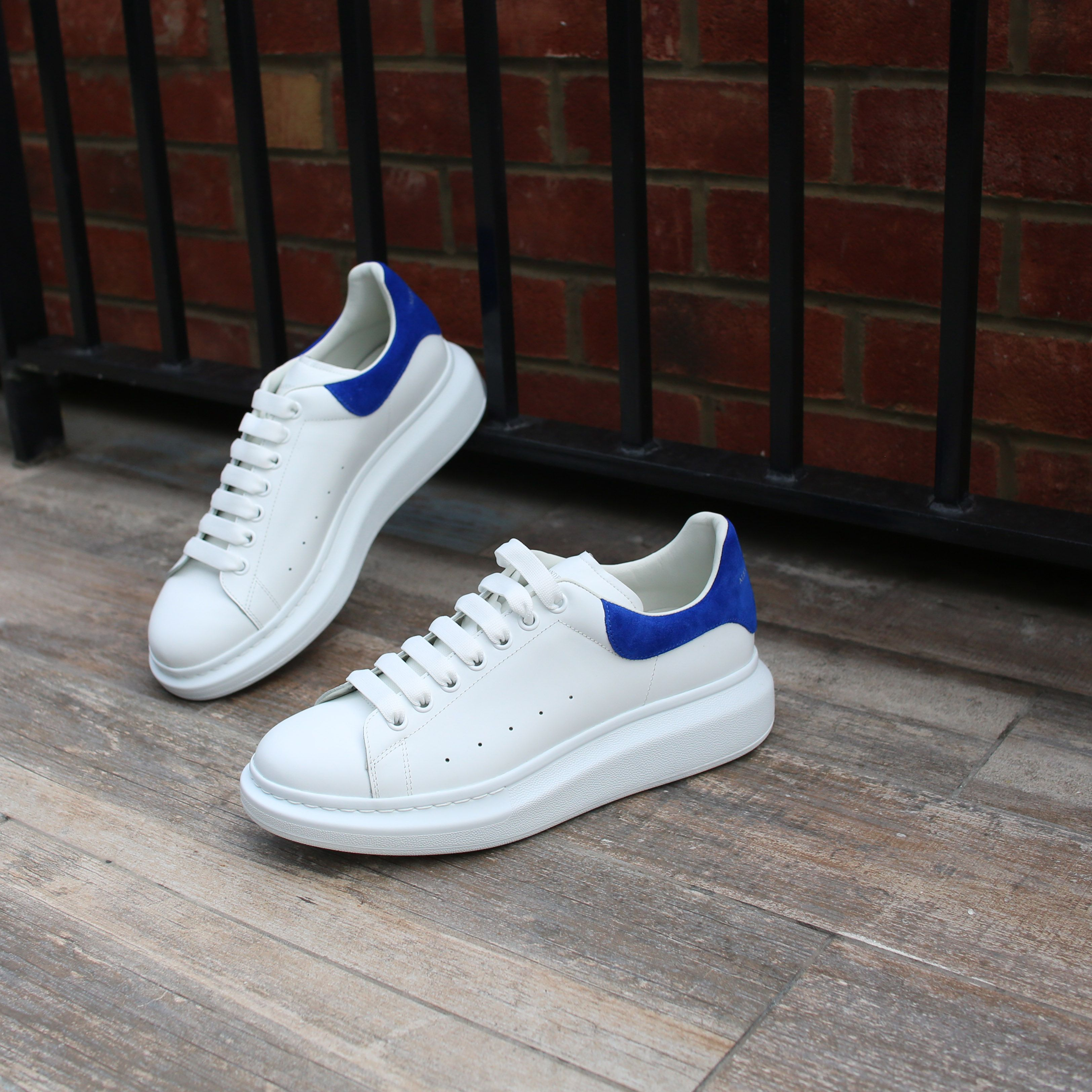 090d11593c17 Alexander McQueen Larry white leather trainers with a royal blue suede heel  panel. An essential pair of shoes for every wardrobe.