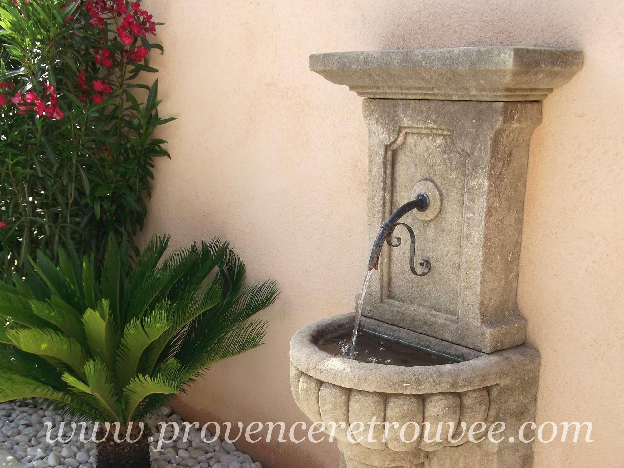 Point d\'eau contre un mur de maison avec la fontaine avec ...