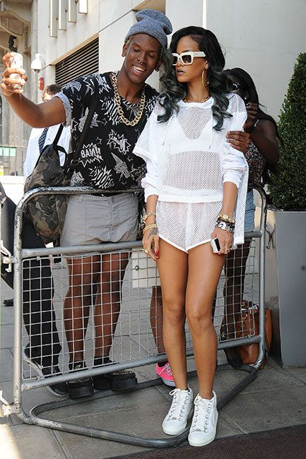 Rihanna poses with a fan while leaving her hotel in London on June 18. Dude, there is no way Riri is going to smile for your photo, she just found out today that she's going grey!