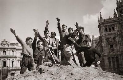Niños con la mano alzada desescombrando La Cibeles