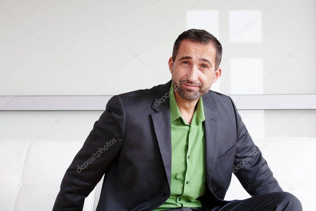 Handsome Smiling Businessman In Suit And Green Shirt Stock Photo