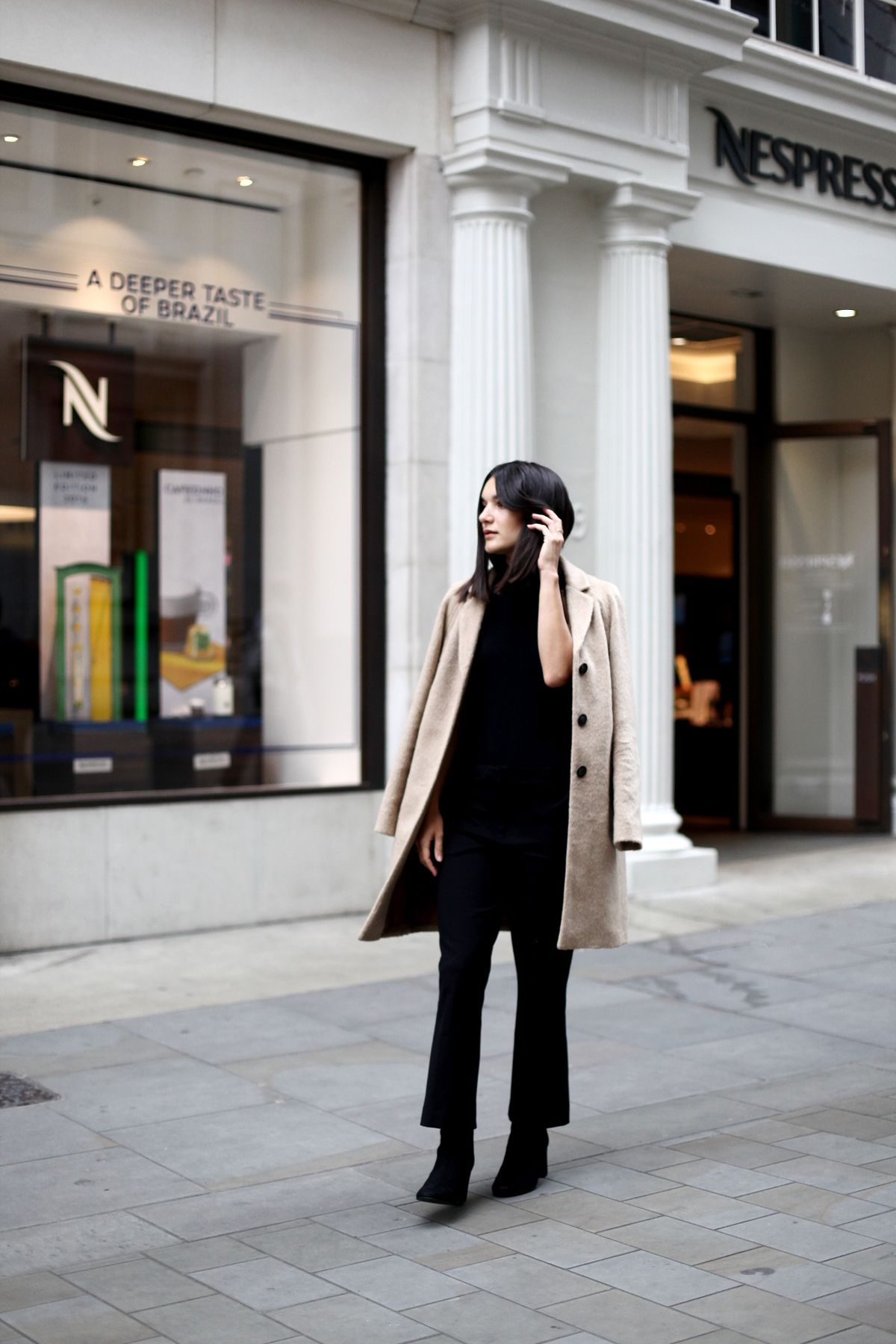 Anisa Sojka styles camel brown Boden coat | Black high-neck ASOS body top with strappy back | Flare crop trousers | Ankle boot with heel | Straight shoulder length brunette hair | Minimal fashion blogger street style shot in London by Alice Reinhardt