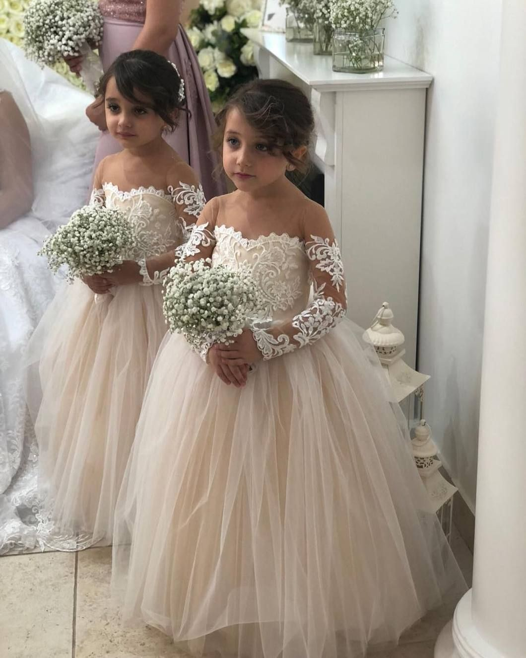 329ca4fce640 Beautiful tulle flower girl dress that is floor length, has off the  shoulder long lace sleeves, and a ball gown silhouette.