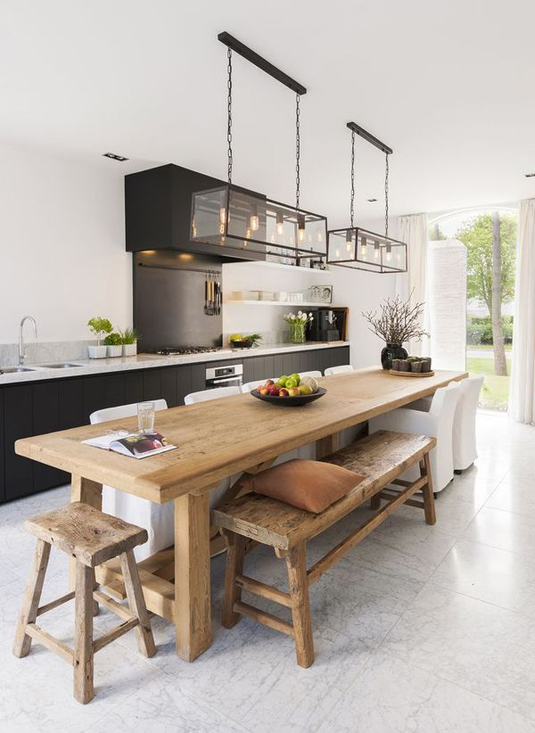 een zwarte keuken met een houten tafel en hele leuke hanglampen