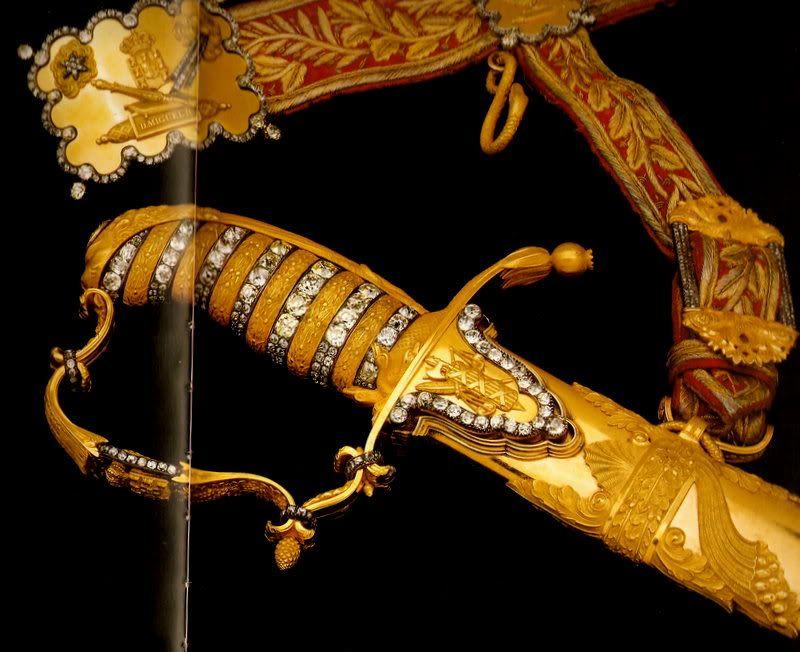 Sabre de Corte com Cinto  Origem: Portugal, Lisboa > 1ª metade do séc. XIX  Materiais: Ouro, Prata Dourada, Brilhantes, Veludo, Aço  Pertença de D. Miguel I