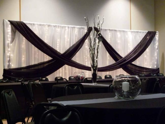 Black swags on fabric backdrop behind head table at wedding reception - Elite Events Rental