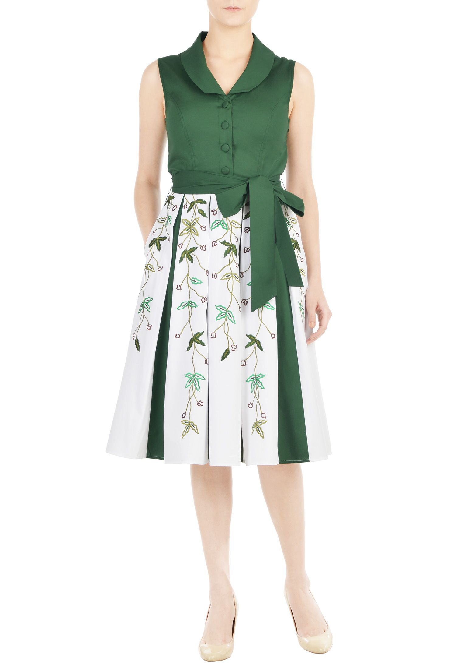 A shawl collar frames the V-neckline of our cotton poplin dress,  cinched at the waist with a sash tie belt and flared out to an inset box pleat skirt with floral vine embellishments.