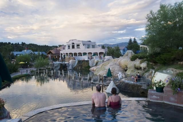 A couple soaks in the natural hot springs at The Springs Resort & Spa at sunset - Pagosa Springs, CO