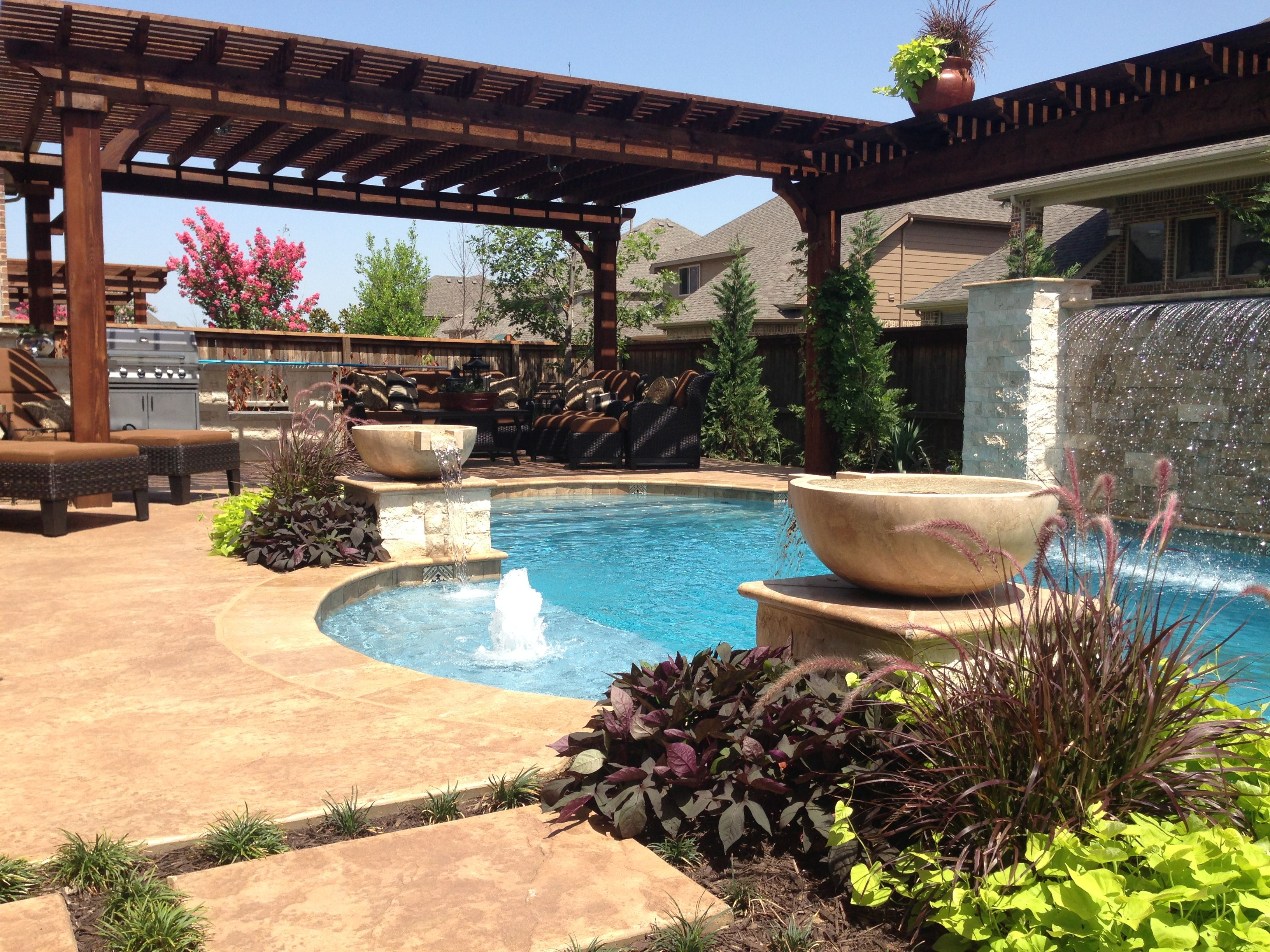 Dolce pools made sheer decent rain curtain water fall from raised wall faced with white stones for Fort worth swimming pool builders