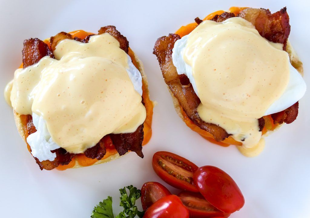 Classic eggs Benedict with hollandaise sauce dripping down the side and tomatoes backing em up. Cla