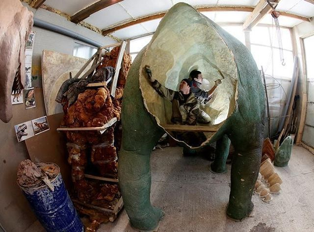 Assistants of businessman Vitaly Yan-Vin-Tin (not pictured) work on a polyurethane and fibreglass sculpture of a dinosaur in the Siberian village of Beryozovka outside Krasnoyarsk, Russia, February 17, 2017. The Yan-Vin-Tin Sculptures Workshop produces various sculptures made of bronze, clay, fiber-reinforced concrete, fibreglass and other materials for the decoration of city parks, private manors and interiors. REUTERS/Ilya Naymushin