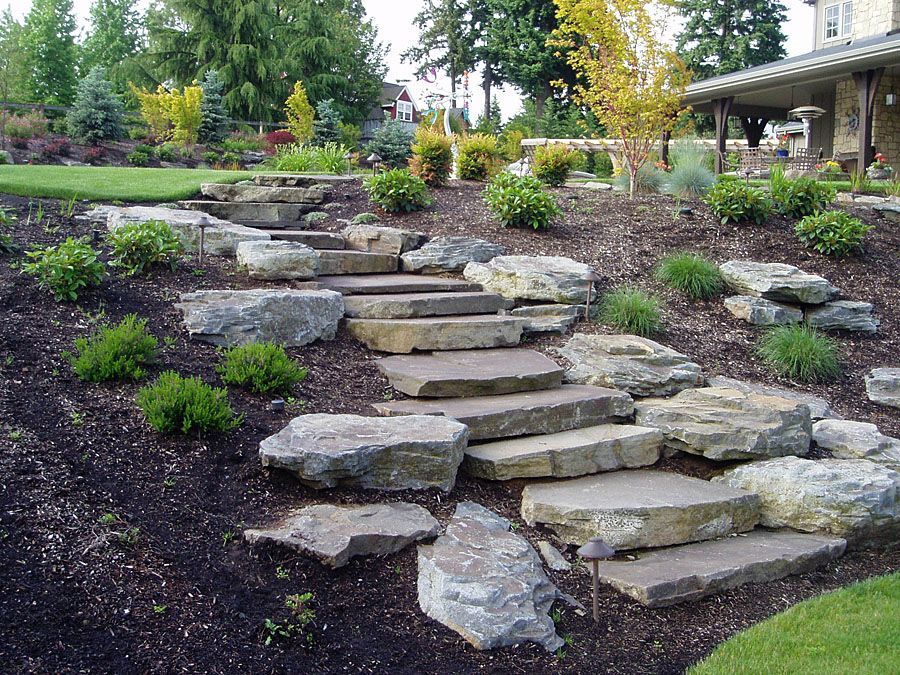 Slope landscaping with stone hardscapes patios walls for Rock stepping stones landscaping