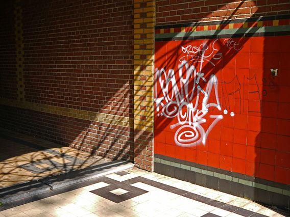 Nieuw in mijn Werk aan de Muur shop: Kerk-portaal met graffiti en schaduw-lijnen op de wand door zon-licht; foto Kattenburgergracht in Am