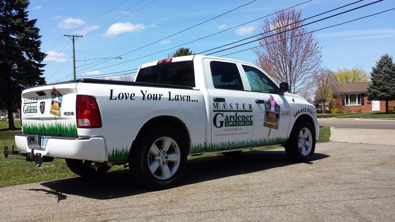 master gardener logo co name on the front doors and tailgate catch phrase on the side of bed with grass along the bot work truck commercial vehicle fleet master gardener logo co name on