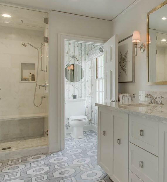 Gray and white master bathroom boasts a seamless glass walk in shower fitted…